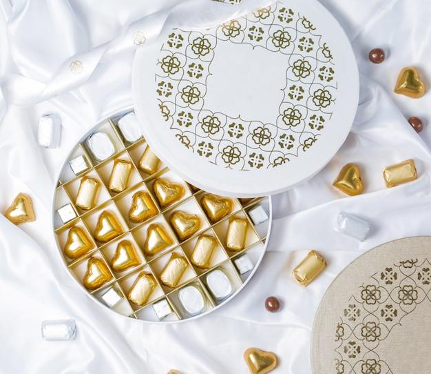 Vista superior de la caja redonda de chocolate con bombones envueltos en oro y plata
