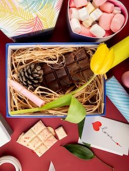 Vista superior de una caja de regalo abierta con flor de tulipán de color amarillo, barra de chocolate oscuro, cono y paja y una caja en forma de corazón llena de malvaviscos en la mesa de color rojo oscuro