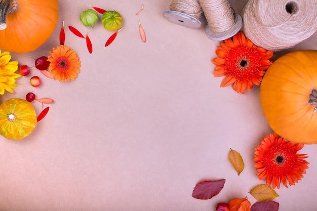 Vista superior de la caja de regalo artesanal, flores amarillas y naranjas y calabazas sobre fondo rosa