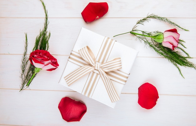 Vista superior de una caja de regalo atada con lazo y rosas de color rojo con pétalos dispersos y espárragos sobre fondo blanco de madera