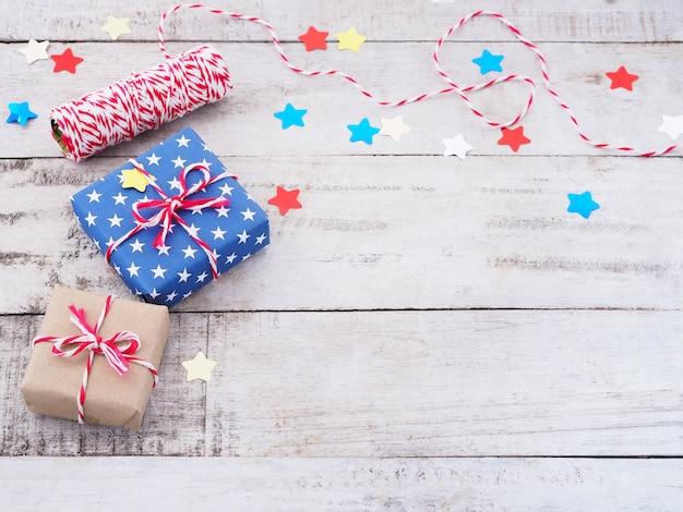 Vista superior de la caja de regalo y confeti estrella sobre fondo de madera vintage.