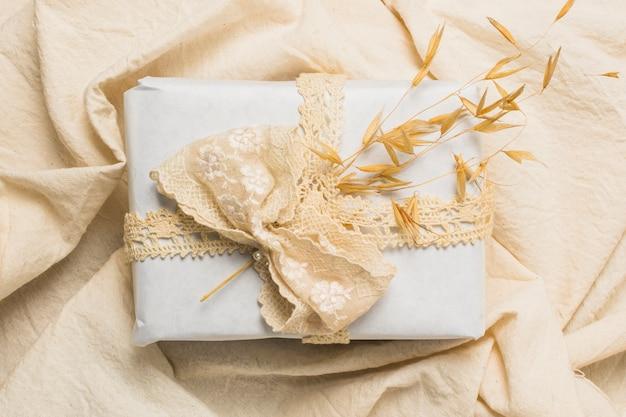 Vista superior de caja de regalo decorada sobre textil arrugada.