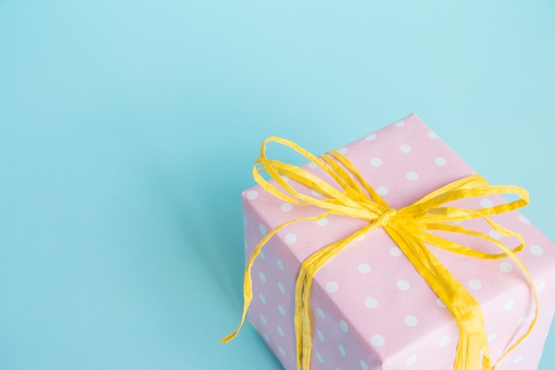 Vista superior de una caja de regalo envuelta en papel punteado rosa y lazo amarillo atado sobre azul claro.