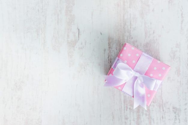 Vista superior de una caja de regalo envuelta en papel punteado rosa y lazo de satén atado sobre madera blanca.