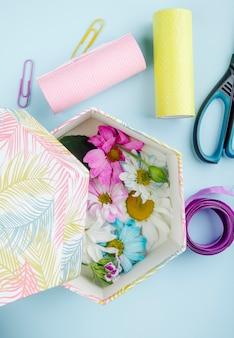 Vista superior de una caja de regalo llena de coloridas flores de crisantemo con margaritas y tijeras rollos de papel de colores y cinta morada sobre fondo azul.