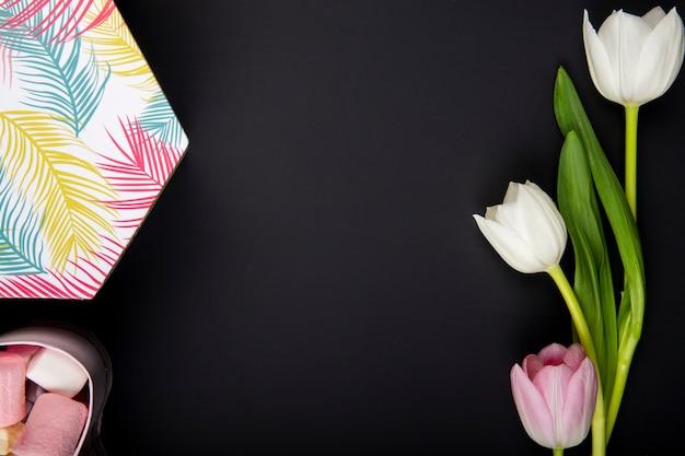 Vista superior de una caja de regalo llena de malvaviscos y tulipanes de color blanco y rosa sobre mesa negra con espacio de copia