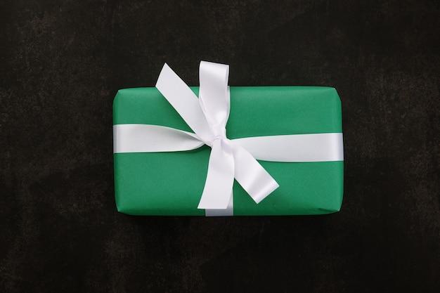 Vista superior de la caja de regalo de navidad envuelta con papel verde y cinta blanca sobre negro
