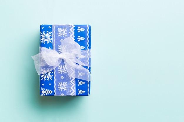 Vista superior caja de regalo de navidad con lazo blanco sobre fondo azul con espacio de copia