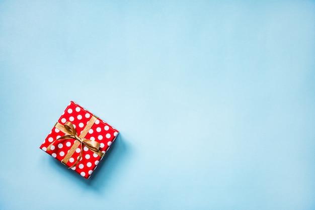 Vista superior de una caja de regalo de puntos rojos atados con lazo dorado sobre fondo azul. copia espacio