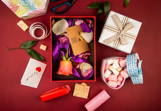 Vista superior de una caja de regalo roja con tarjeta de papel marrón y flor color de rosa coral y pétalos con cinta morada y caja en forma de corazón llena de malvavisco en la mesa de color rojo oscuro