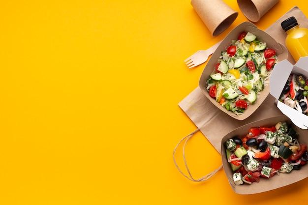 Vista superior cajas con ensalada sobre fondo amarillo