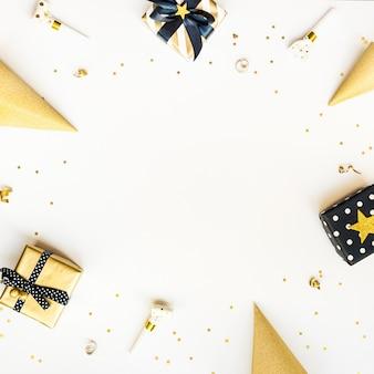 Vista superior de cajas de regalo y accesorios de fiesta en varios colores negro, blanco y dorado.
