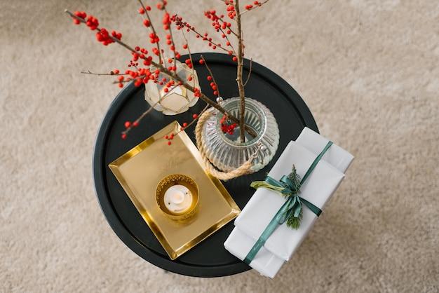 Vista superior de cajas de regalo atadas con una cinta de esmeralda con una ramita de abeto, una vela, un jarrón de bayas rojas y una bandeja de oro.