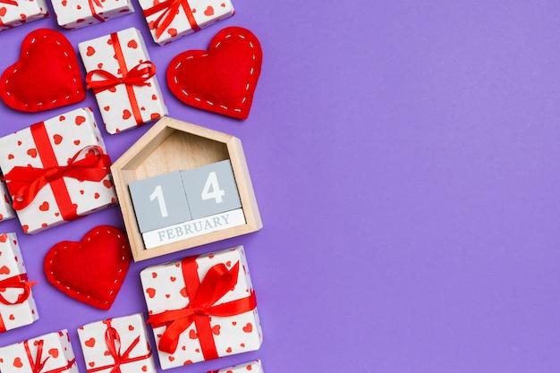 Vista superior de cajas de regalo, calendario de madera y corazones textiles rojos en colores. el catorce de febrero. día de san valentín