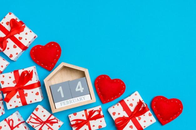 Vista superior de cajas de regalo, calendario de madera y corazones textiles rojos sobre fondo colorido. el catorce de febrero. concepto de san valentín con espacio de copia
