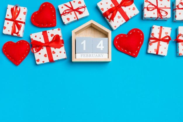 Vista superior de cajas de regalo, calendario de madera y corazones textiles rojos sobre mesa. el catorce de febrero.