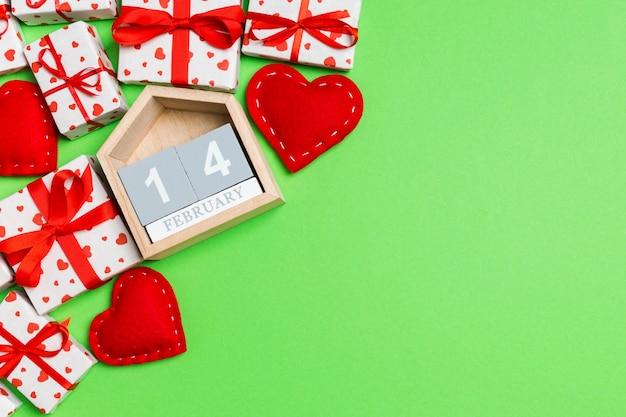 Vista superior de cajas de regalo, calendario de madera y corazones textiles rojos sobre verde