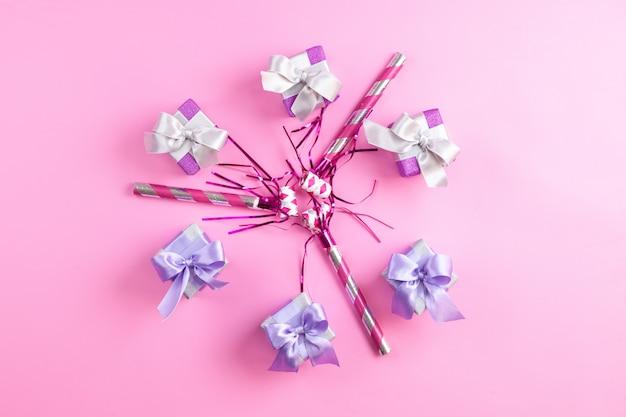 Una vista superior de cajas de regalo de color púrpura junto con silbatos de cumpleaños aislados