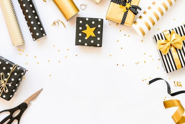 Vista superior de cajas de regalo y materiales de envoltura en varios colores negro, blanco y dorado.