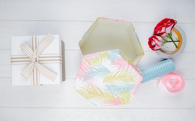 Vista superior de cajas de regalo y rosas de color rojo con rollos de cinta adhesiva y cinta rosa sobre fondo blanco de madera