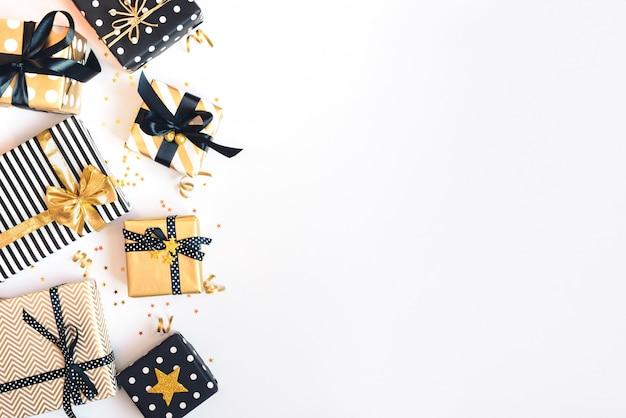 Vista superior de cajas de regalo en varios colores negro, blanco y dorado.