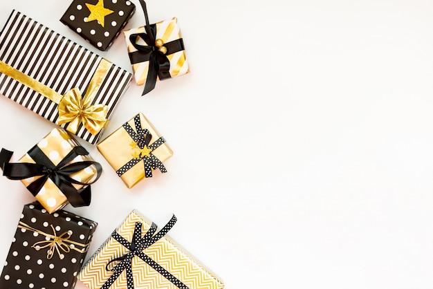 Vista superior de cajas de regalo en varios negro, blanco y dorado.
