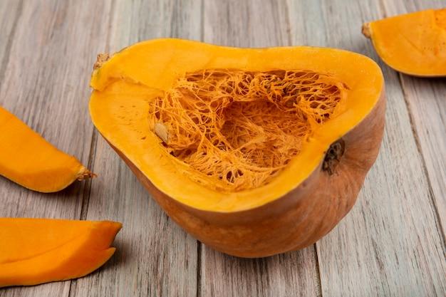 Vista superior de calabaza nutritiva naranja con sus semillas con cáscaras de calabaza aisladas sobre una superficie de madera gris