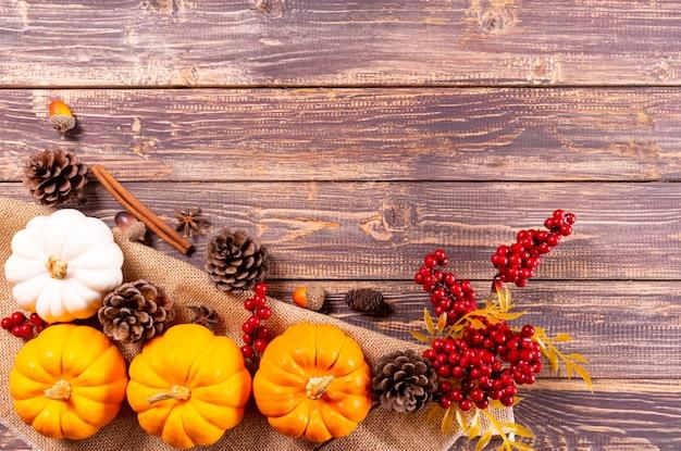 Vista superior de calabazas, bayas rojas y piña sobre fondo de madera vieja. marco del día de acción de gracias