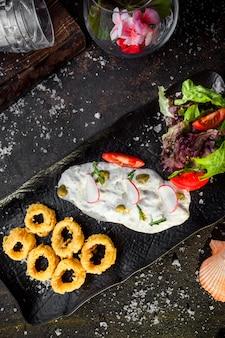 Vista superior de calamares rebozados con salsa y ensalada de verduras frescas en la bandeja