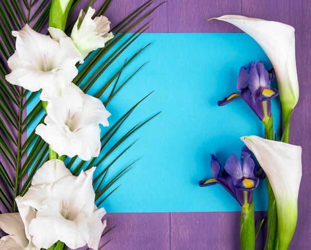 Vista superior de calas y gladiolos de color blanco con flor de iris morado oscuro y hoja de palma con una hoja de papel azul sobre fondo morado