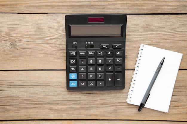 Vista superior calculadora de mesa de oficina con lápiz y cuaderno sobre la mesa para negocios con espacio de copia.