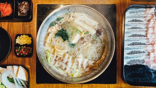 Vista superior del caldo shabu caliente e hirviendo con col, eryngii, enotitake, tofu y cerdo kurobuta