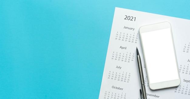Vista superior del calendario 2021 en blanco con el teléfono inteligente de pantalla en blanco sobre fondo de color azul