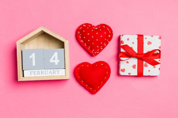 Vista superior del calendario de madera, cajas de regalo blancas y corazones textiles rojos en colores. día de san valentín