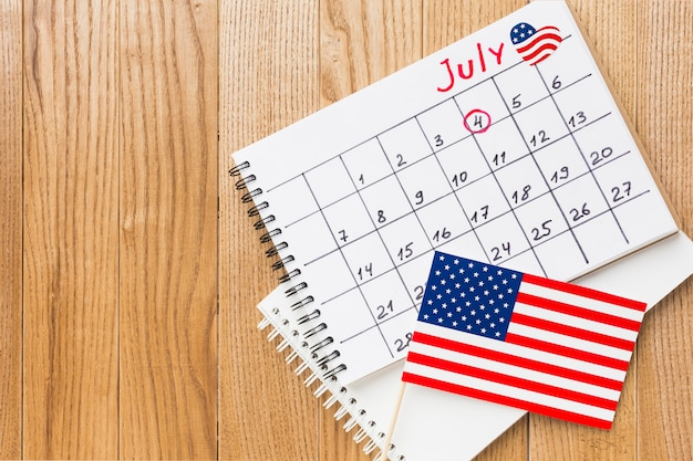 Vista superior del calendario del mes de julio con banderas americanas y espacio de copia