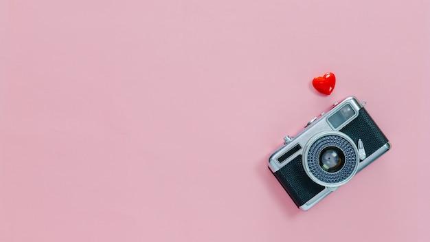 Vista superior de la cámara antigua vintage y pequeño corazón rojo sobre fondo rosa pastel.