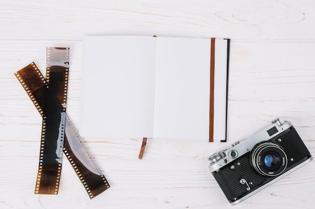 Vista superior cámara con cuaderno y negativos