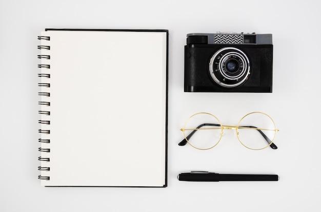 Vista superior de la cámara de fotos vintage con un bloc de notas