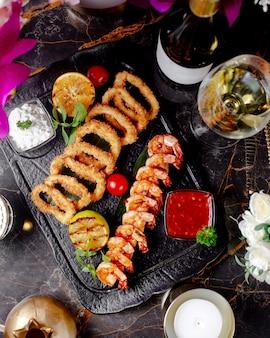 Vista superior de camarones fritos y calamares servidos con salsas de chile dulce y yogurt