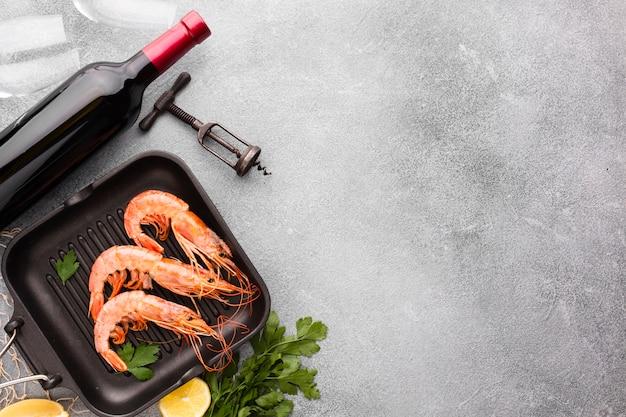 Vista superior de camarones en sartén con botella de vino