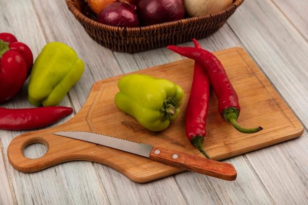 Vista superior de la campana y los chiles en una tabla de cocina de madera con un cuchillo con cebollas en un balde en una pared de madera gris