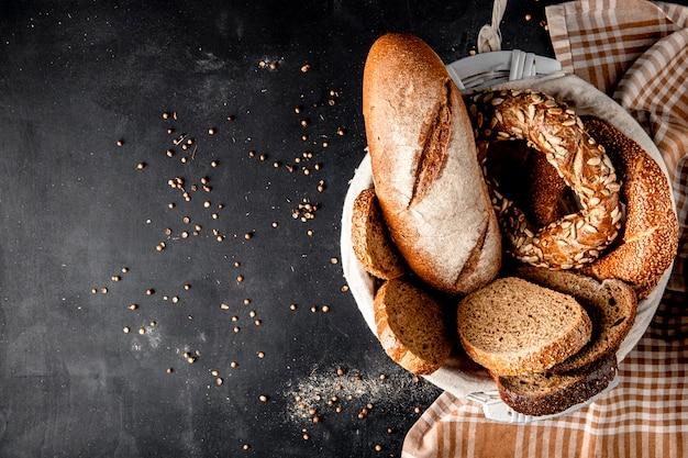 Vista superior de la canasta llena de panes como baguette bagel centeno con semillas de girasol en superficie negra