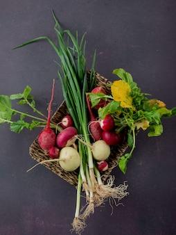 Vista superior de la canasta llena de verduras como rábanos rojos y blancos cebollín sobre fondo granate con espacio de copia