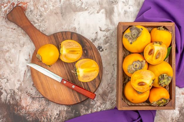 Vista superior caquis deliciosos un cuchillo en la tabla de cortar caquis caja chal púrpura sobre fondo desnudo