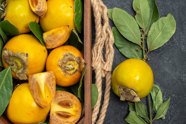 Vista superior caquis dulces frescos dentro de la caja en la mesa oscura sabor a fruta madura
