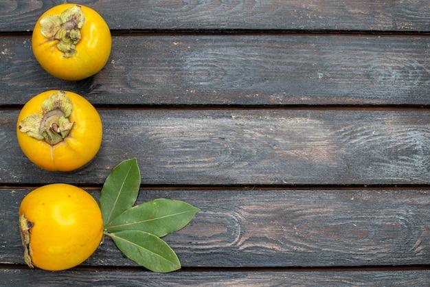 Vista superior de los caquis frescos en la mesa rústica de madera, fruta madura madura