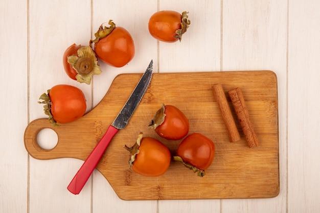 Vista superior de caquis suaves sobre una tabla de cocina de madera con ramas de canela con un cuchillo sobre una superficie de madera blanca