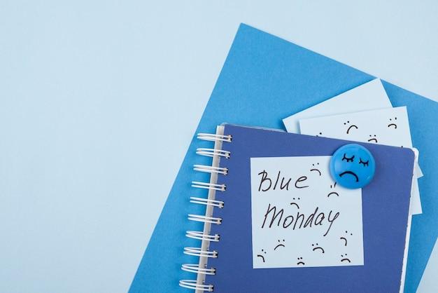 Vista superior de la cara triste con cuaderno y notas adhesivas para el lunes azul