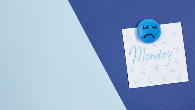 Vista superior de la cara triste con espacio de copia y nota adhesiva para el lunes azul