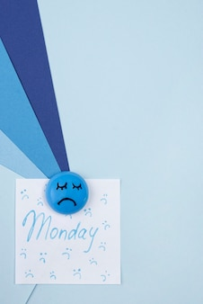 Vista superior de la cara triste con nota adhesiva y espacio de copia para el lunes azul